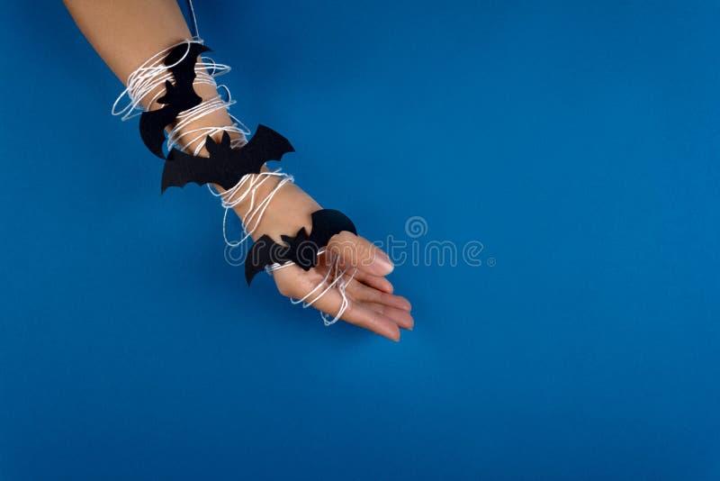 Женственная рука в оболочке в белой сети с черными бумажными летучими мышами на голубой предпосылке удерживания halloween даты пр стоковое изображение rf