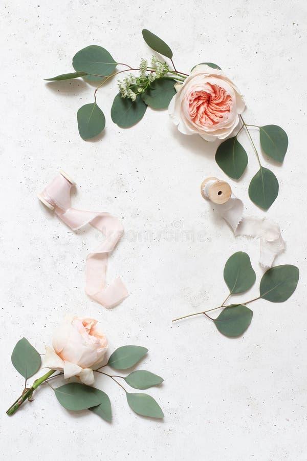 Женственная свадьба, сцена натюрморта дня рождения Ленты шелка, листья эвкалипта и покраснеть розовые английские цветки роз стоковое фото
