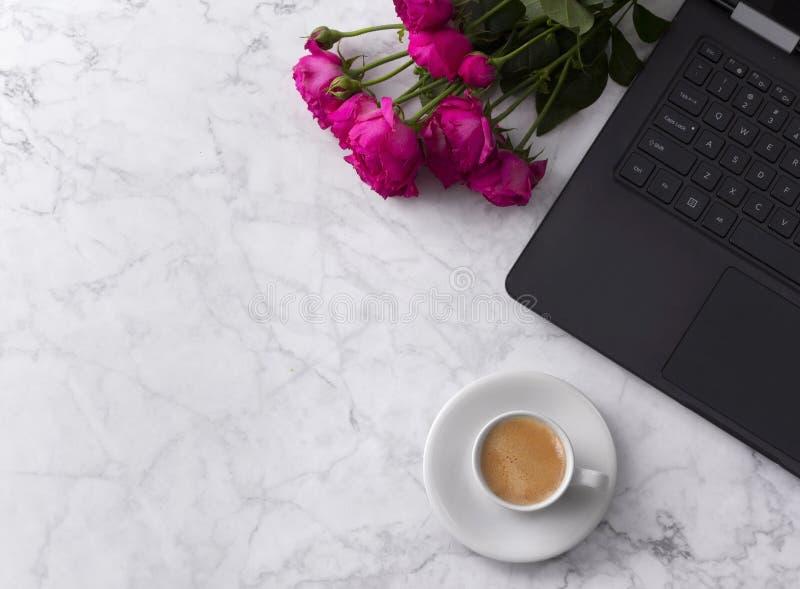 Женственное место для работы с ноутбуком, букет роз и кофе на мраморной таблице стоковое изображение rf