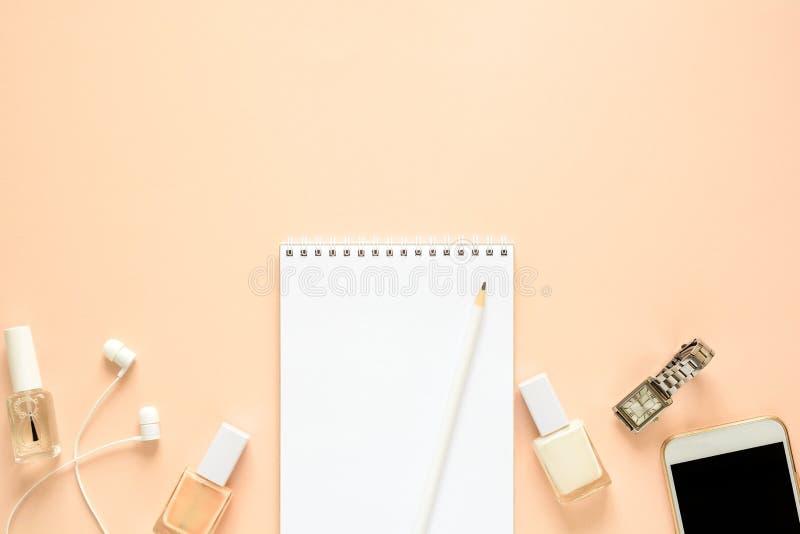Женственное место для работы с smartphone, наушниками, тетрадью, карандашем, маникюром и часами Плоское положение стоковая фотография