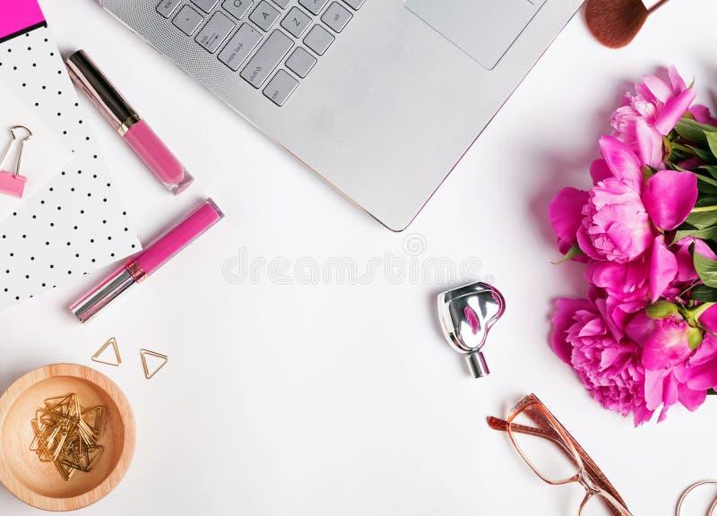 Женственное рабочее место с компьтер-книжкой и цветками стоковые фото