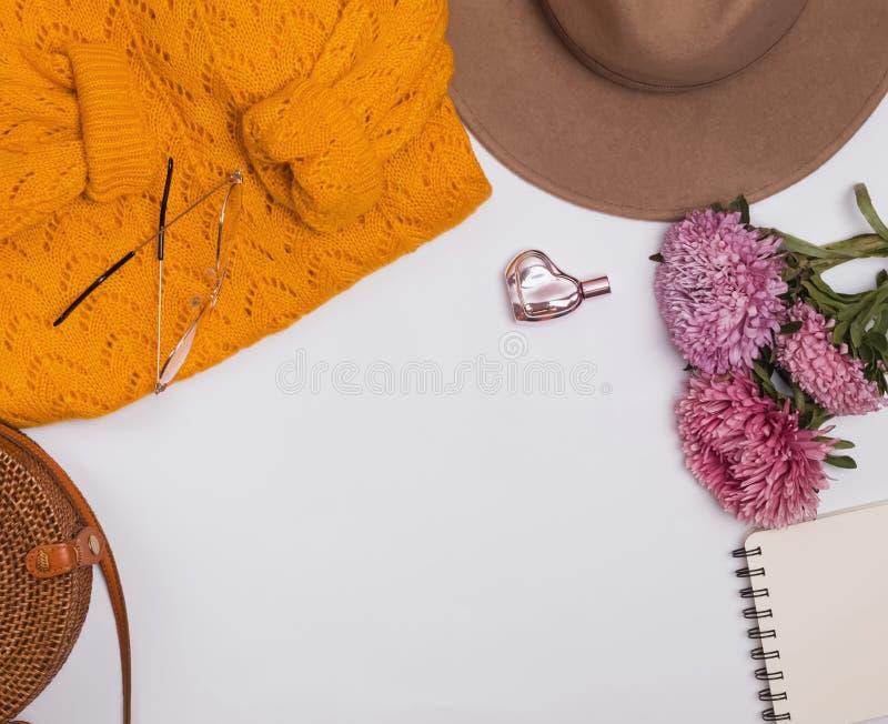 Женственные аксессуары осени: фетровая шляпа, желтый свитер, сумка и цветки стоковое изображение rf