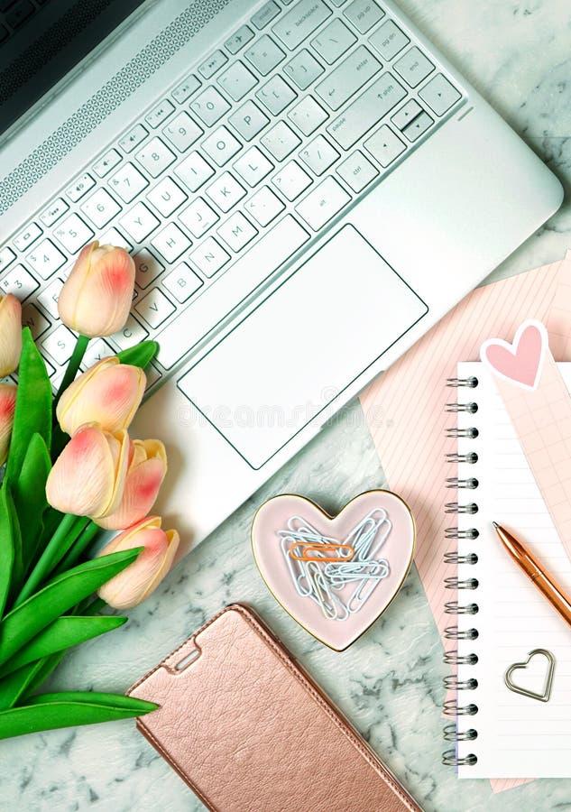Женственный стол с современными аксессуарами золота ноутбука и розы экрана касания стоковые фотографии rf