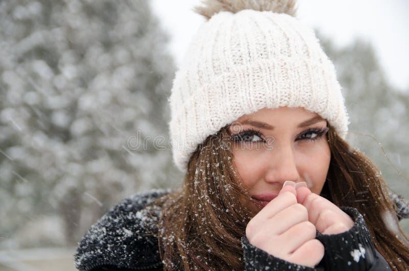 Женщина Î'eautiful пока свой идти снег с замерзая руками стоковая фотография