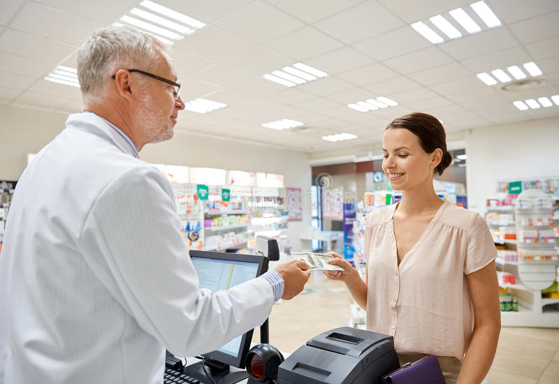 Женщина давая деньги к аптекарю на аптеке стоковые изображения