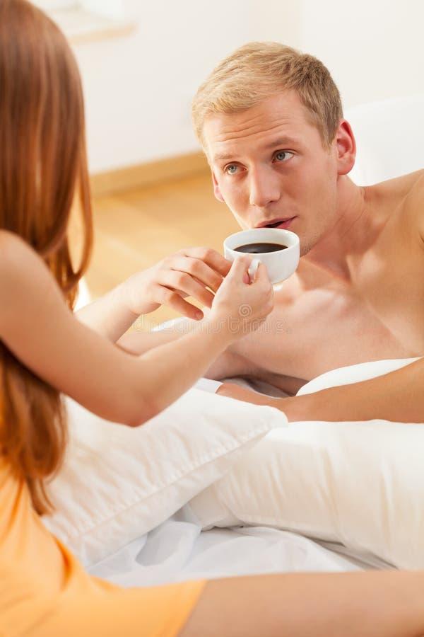 Женщина давая кофе к человеку в кровати стоковое фото