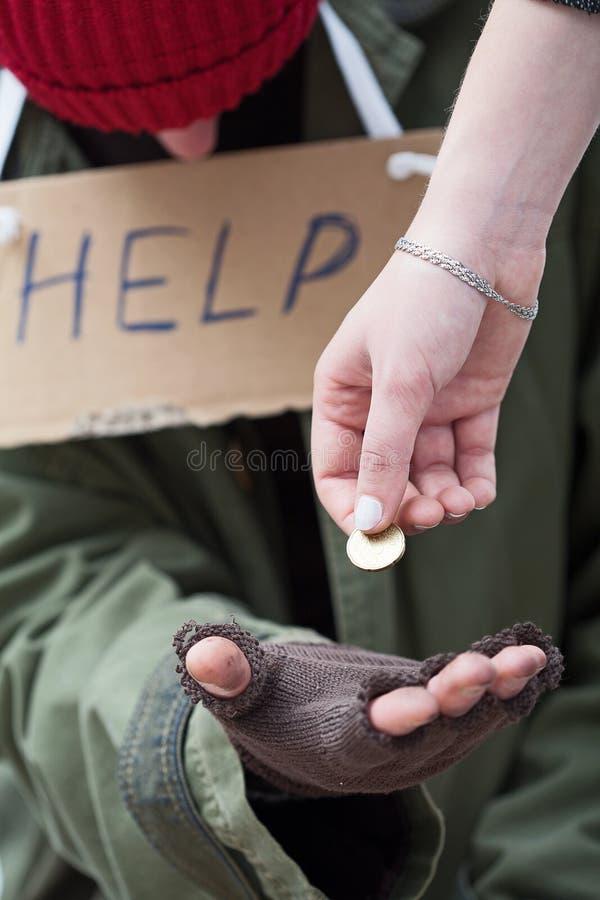 Женщина давая монетку к бездомному человеку стоковые фотографии rf