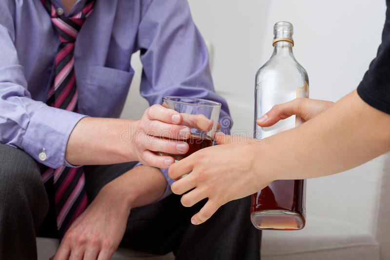 Женщина давая питье к его супругу стоковая фотография