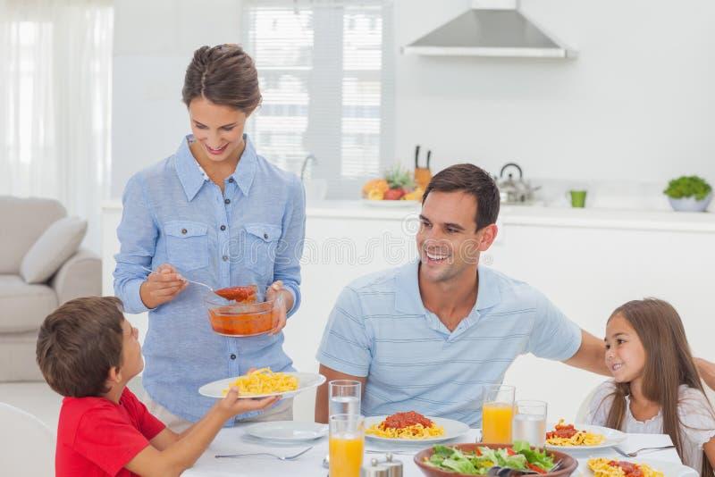 Женщина давая соус для пасты к ее сыну стоковое фото
