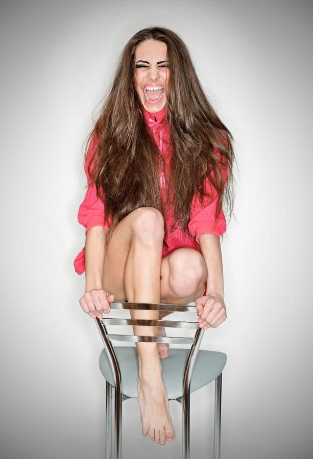 женщина агрессивныйого пинка взволнованности кофточки кричащая стоковое фото