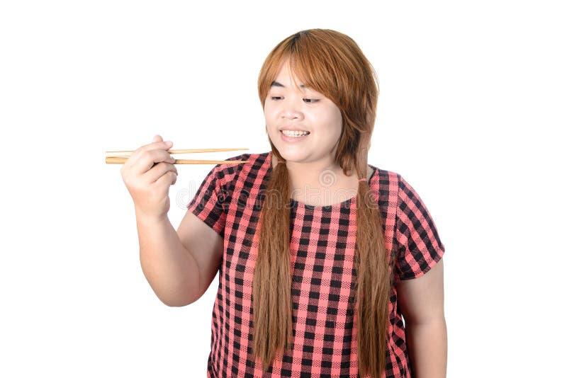 Женщина азиата толстенькая держа палочки, изолированные на белом backgrou стоковые фотографии rf