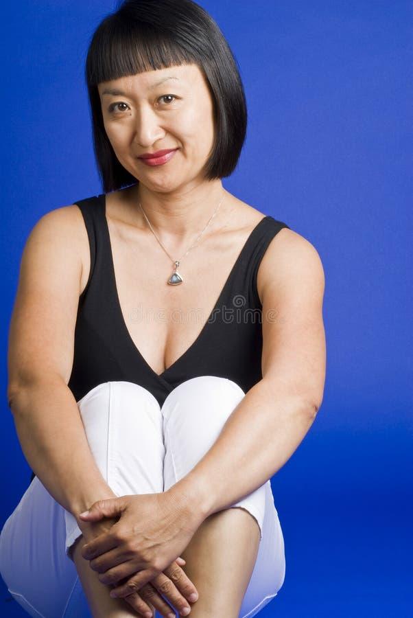 женщина азиатских волос короткая сидя сь стоковое фото rf