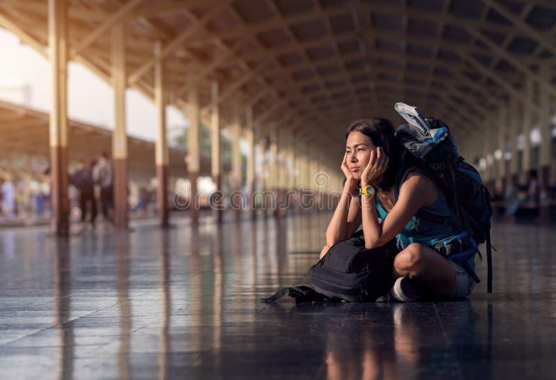 Женщина Азии с рюкзаком сумки и сидеть пробуренный для ожидания времени для t стоковые изображения rf