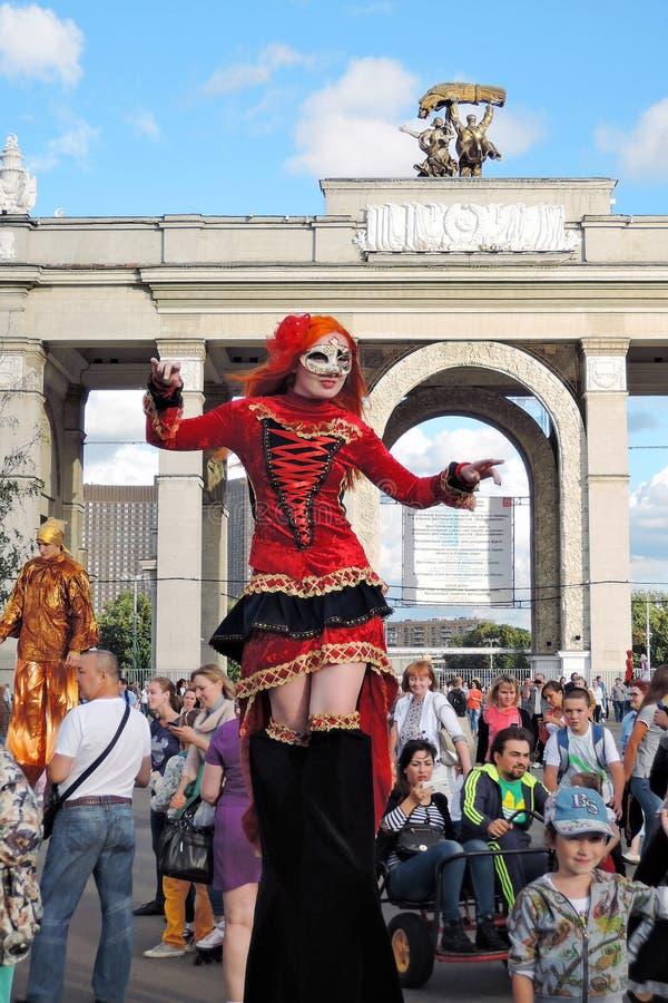 Женщина актера улицы представляет для фото в красном платье стоковые изображения