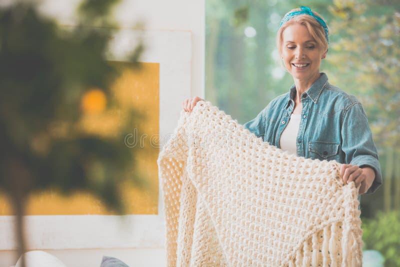 Женщина аранжирует белое покрывало стоковое фото