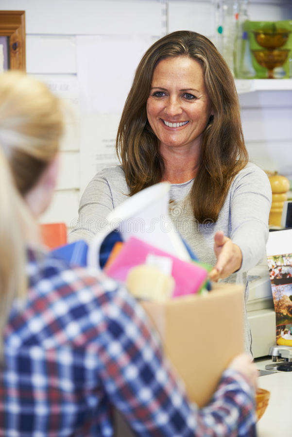 Женщина даря излишние детали к магазину призрения стоковое фото rf