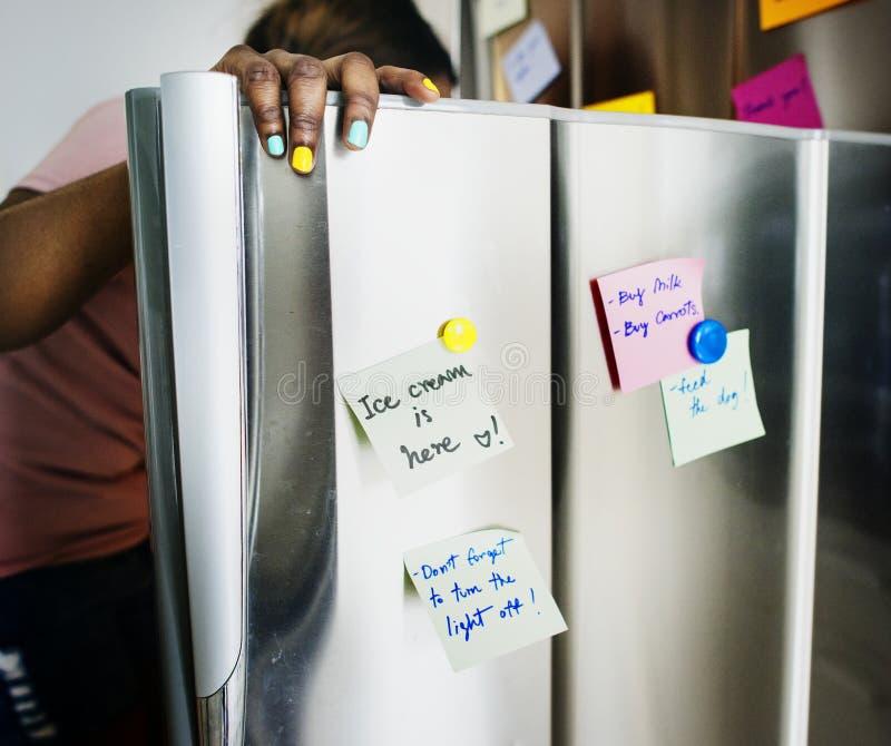 Женщина африканского происхождения раскрывая холодильник стоковая фотография