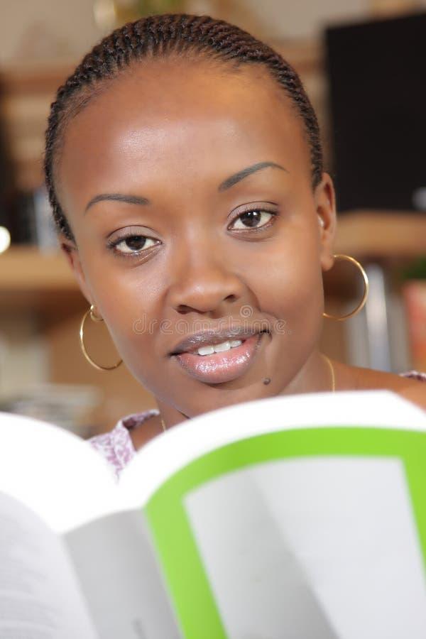 Женщина афроамериканца изучая и работая стоковое фото