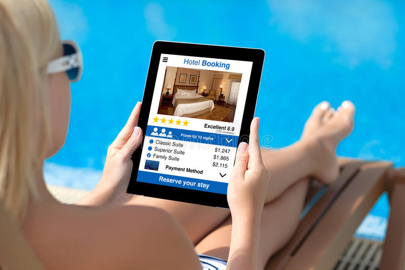 Женщина бассейном держа таблетку с экраном бронирования гостиниц app стоковое изображение rf