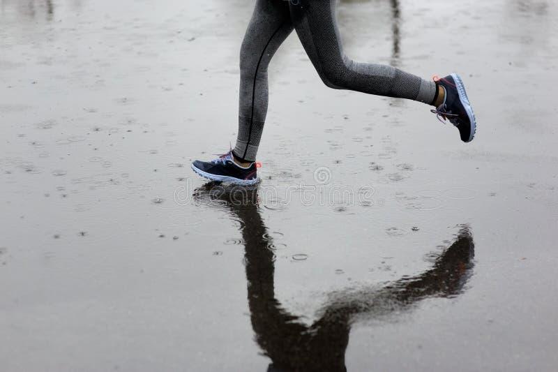 Женщина бегуна бежать в парке в дожде Jogging тренировка для m стоковые изображения rf