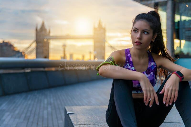 Женщина бегуна отдыхая после встречи разминки в Лондоне стоковое изображение