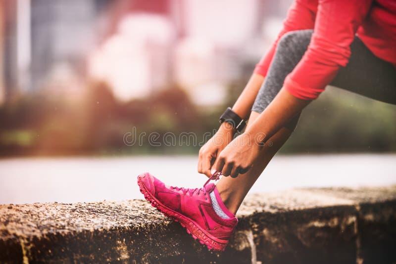 Женщина бегуна получая готовый побежать связывать шнурки ботинок бега Крупный план мотивации здорового образа жизни jogging обуви стоковое изображение