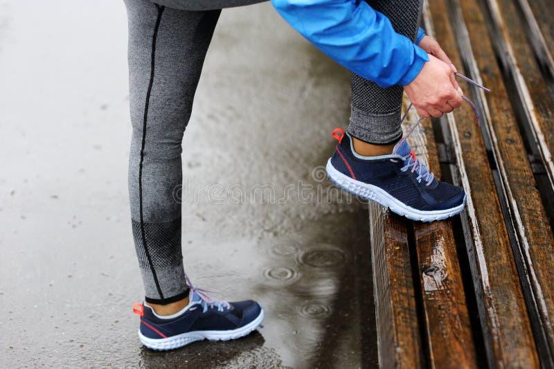 Женщина бегуна связывая шнурки перед тренировкой в дожде Марафон стоковая фотография rf
