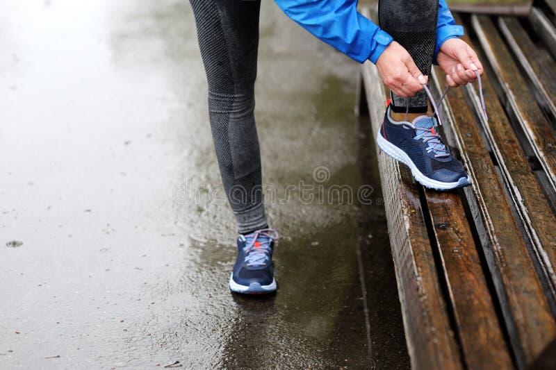 Женщина бегуна связывая шнурки перед тренировкой в дожде Марафон стоковое фото rf