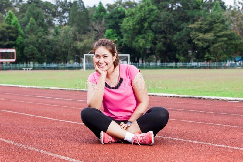 Женщина бегуна усмехаясь на следе стоковая фотография