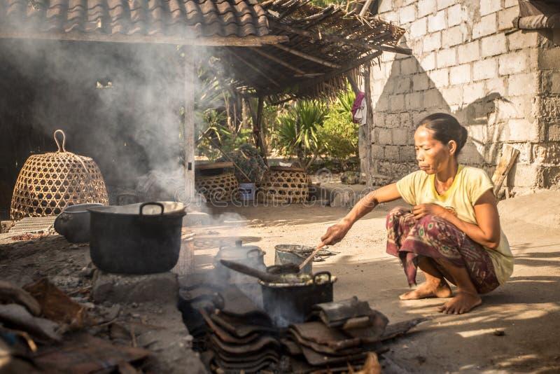 Женщина бедности варит еду используя основные предметы первой необходимости стоковые фото
