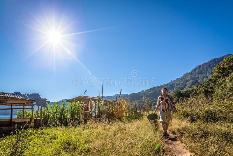 Женщина бедности делает ее прачечную на солнечный день, Бали, Индонезию стоковое фото