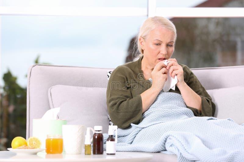 Женщина беды зрелая страдая от кашля дома стоковая фотография