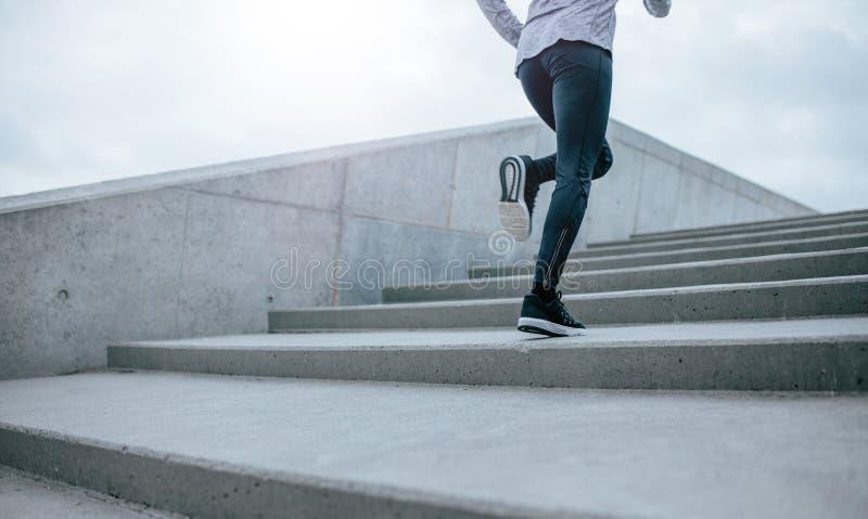 Женщина бежать вверх лестница стоковые изображения