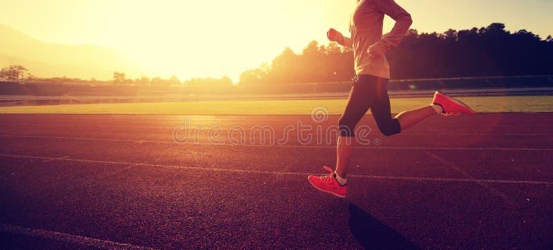 Женщина бежать во время солнечного утра на следе стадиона стоковые фото
