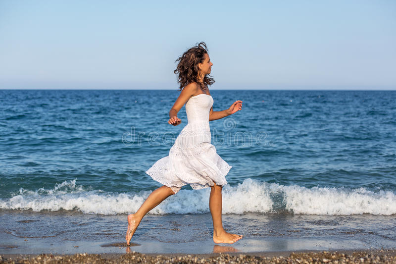 Женщина бежать вдоль пляжа стоковая фотография rf