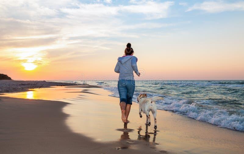 Женщина бежать на пляже стоковая фотография