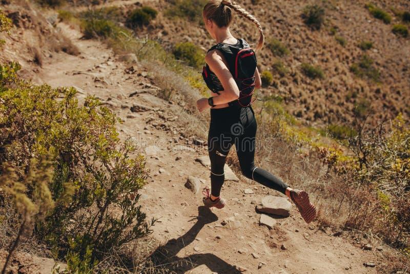 Женщина бежать на скалистых следах в горах стоковое изображение