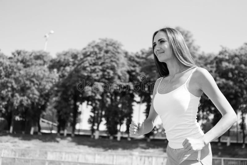 Женщина бежать на следе арены стоковое фото rf