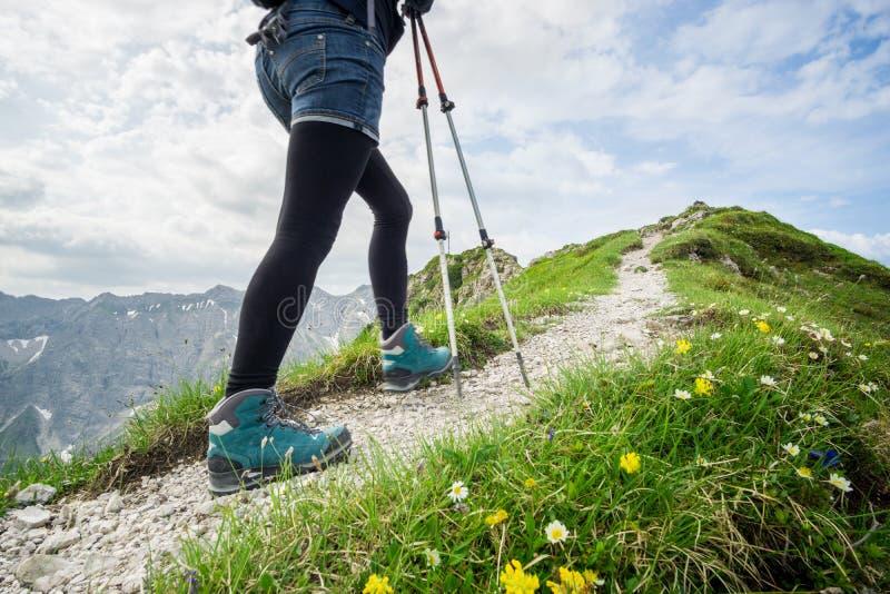Женщина бежать на узкой горной тропе с пешими поляками стоковая фотография rf