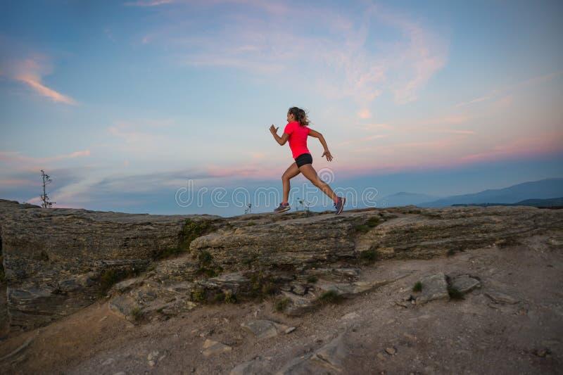 Женщина бежать на утесах Женские по пересеченной местности бежать в горах стоковые фото