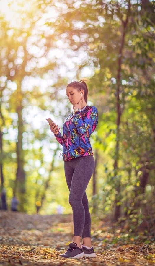 Женщина бежать нося Smartwatch спорта и беспроводные наушники стоковые изображения