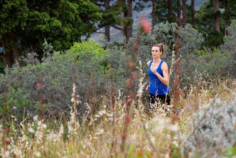 Женщина бежать через поле снаружи стоковое изображение rf