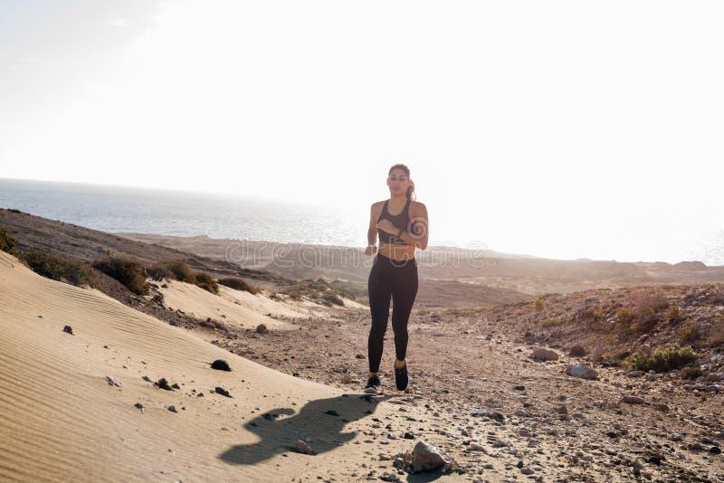 Женщина бежать через скалистую песчанную дюну стоковые изображения