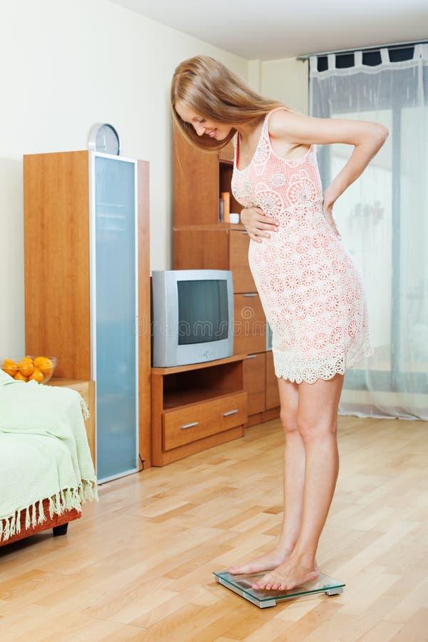 Женщина беременности стоя на масштабах ванной комнаты стоковое изображение rf