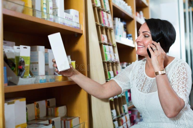 Женщина беседуя телефоном пока ходящ по магазинам в аптеке стоковая фотография rf