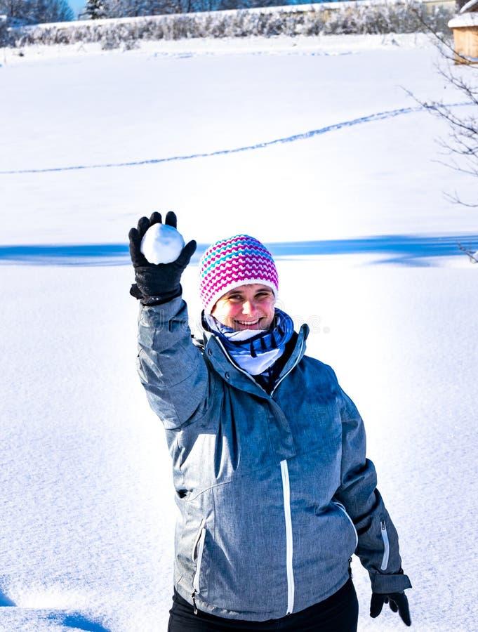 Женщина бросает снежный ком на меня стоковое фото