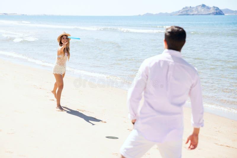Женщина бросая диск летания на пляж стоковое изображение