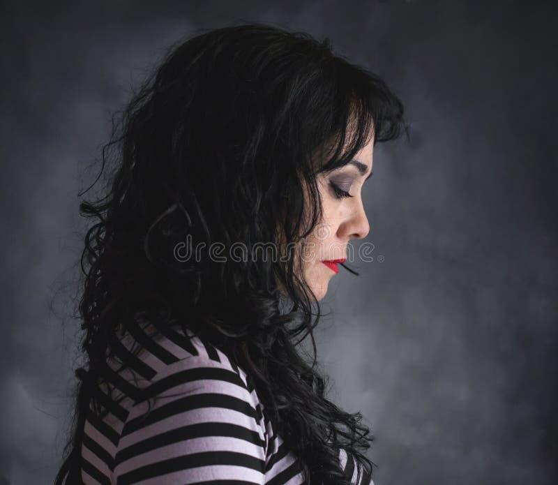 Женщина брюнета в профиле с striped рубашкой стоковое фото rf