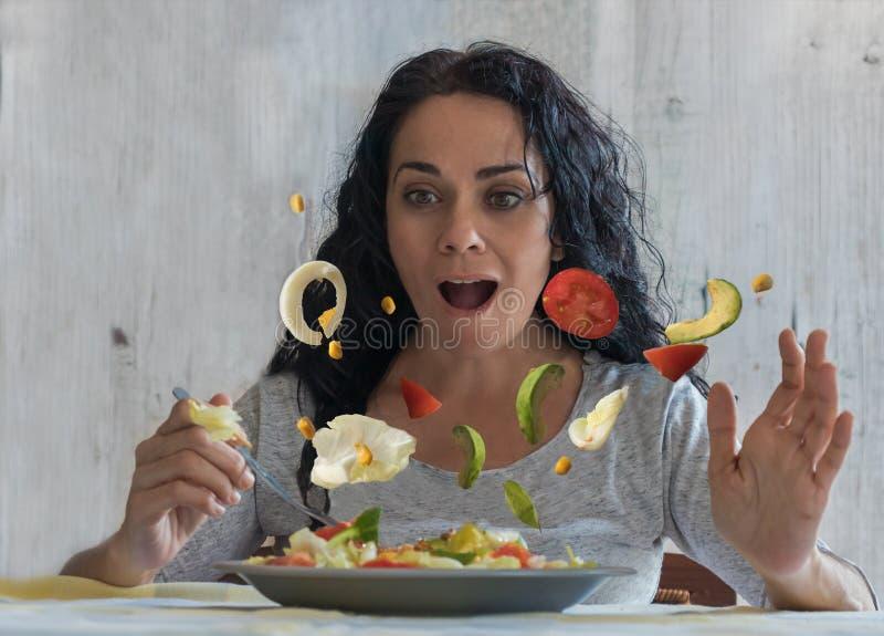 Женщина брюнета смотря удивленный как овощи в ее начале салата лететь стоковое изображение rf