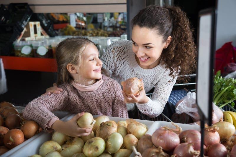 Женщина брюнета с маленькой белокурой девушкой рассматривая луки шарика в магазине стоковое изображение
